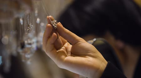 кулон : Woman choosing jewelry pendant in boutique, expensive diamond gift, wealth