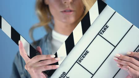 színésznő : Pretty blonde actress posing for audition with movie clapper board.