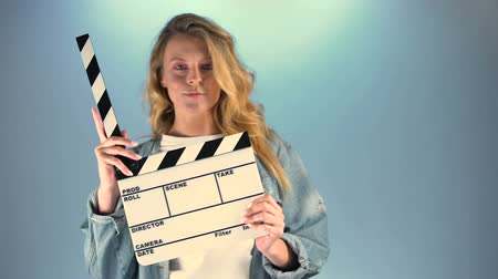 filmmaker : Beautiful long-haired woman holding clapper-board and looking into camera, hobby