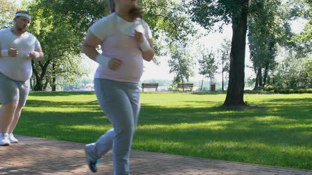 bodyweight : Motivated man and woman jogging in park, outdoor workout, overweight people Stock Footage