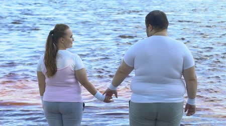 весить : Obese man taking girlfriends hand, couple enjoying beautiful view of river