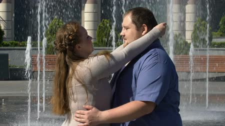 darling : Beautiful plump woman tenderly hugging her obese boyfriend, outdoor date slow-mo