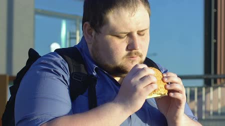 нездоровое питание : Fat male student eating high-calorie burger outdoors, fast food and overweight