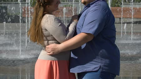 любовь : Happy girlfriend hugging her overweight boyfriend, enjoying romantic date
