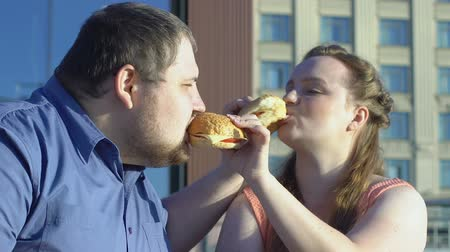 sedentary : Happy plus size couple treating each other fatty burgers on date.