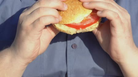 gres : Overweight male chewing high-calorie burger, fast food and obesity problem