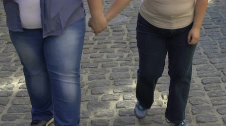 lack : Man and woman with excess weight hardly walking on city street, obesity result