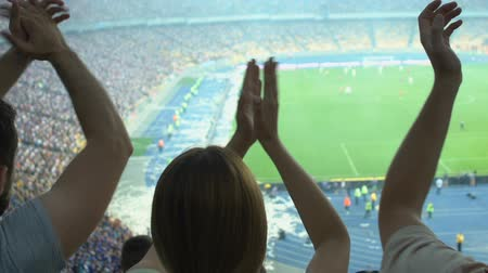 arquibancadas : Football fans clapping supporting team during soccer match on crowded stadium
