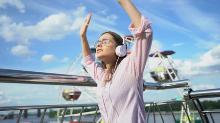 naladit : Happy beautiful brunette dancing in headphones on pier, successful and confident