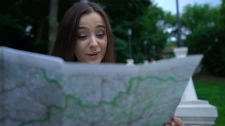 embarrassed : Pretty woman using map to find historical attraction, city tour, new impressions Stock Footage