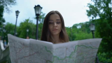 embarrassed : Girl tourist looking at map, successfully finds way to historical attraction