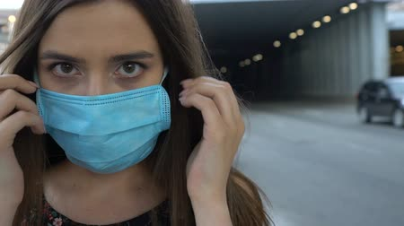 infecção : Woman putting safety mask on city street, environmental pollution, epidemic
