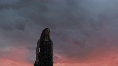 şeytan : Frightened woman walking under scary dark sky, looking around, horror nightmare Stok Video