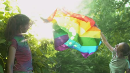 acceptance : Bisexual women waving in wind colorful lgbt flag, protecting their relationship