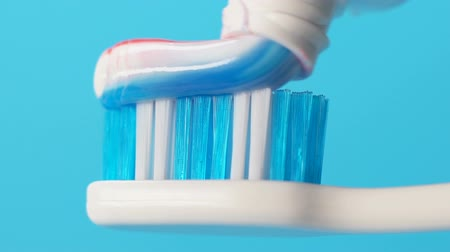 squeeze : Toothpaste squeezed onto toothbrush, oral hygiene, plaque prevention, closeup