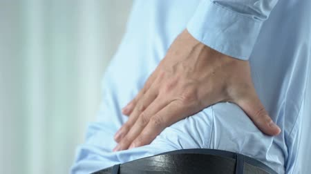 tense : Office worker in 40s feeling sharp back pain, standing up, sedentary lifestyle