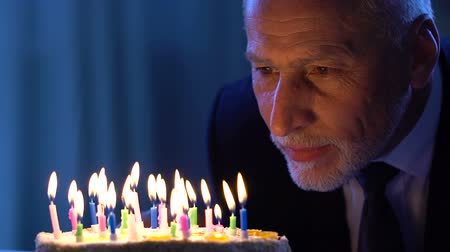 důchodce : Handsome senior male looking at birthday cake making wish, holiday celebration