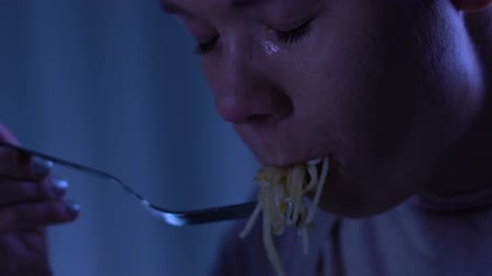 бездомный : Sad woman eating spaghetti and crying, suffering from bulimia, homeless shelter