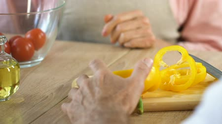 coquettish : Senior woman flirting with husband while he preparing salad, pepper glasses Stock Footage
