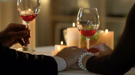 заботливый : Couple drinking wine in romantic evening, man holding woman hands. Стоковые видеозаписи