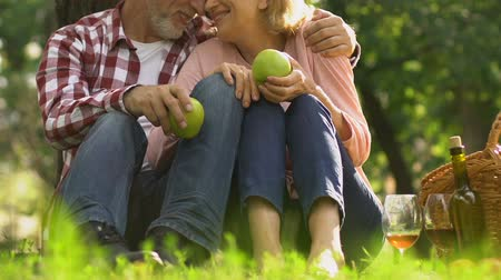 důchodce : Couple holding apples, smiling and hugging, happy in old age, healthy nutrition
