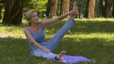 gracefully : Adult gracefully demonstrating yoga poses in park, amateur workout.