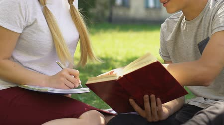 promoce : Smart teenage boy helping girl to do homework outdoors, preparing for exam