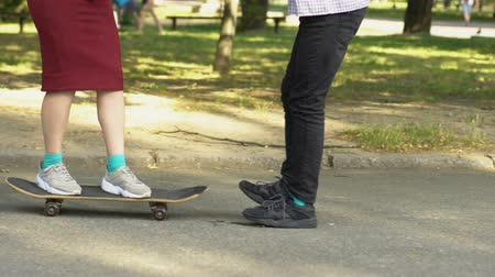 conservative : Boy teaching geek girl to ride skateboard, unusual friendship, youth hobbies