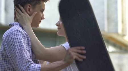 shameful : Teenagers kissing outdoors, hiding faces behind skateboard, shy relationship Stock Footage