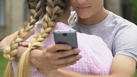 ídolo : Boy texting on smartphone while embracing girlfriend, lie and betrayal, closeup Stock Footage