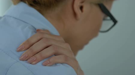 self injury : Female employee concerned about shoulder pain at workplace, self-massage therapy. Stock Footage