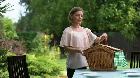 proutěný : Smiling lady puts hamper on table, family dinner outdoors, picnic preparation