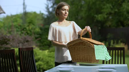cesta : Female placing wicker picnic basket on table, outdoor picnic in country house