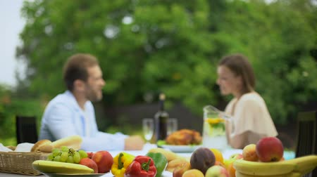 culinária : Young couple talking while having lunch, non gmo fruits, pesticide free food
