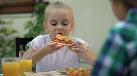 degustation : Girl eating pizza with brother in cafe, celebrating birthday, favourite food Vidéos Libres De Droits
