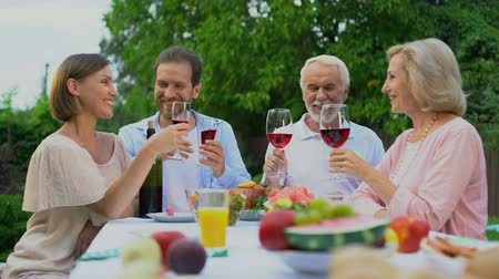 compreensão : Old and middle-aged couples toasting and clinking wine glasses, happy marriage