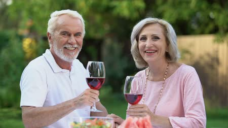 remembering : Smiling old couple celebrating anniversary with wine glasses, family traditions.