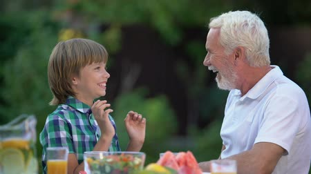 avondmaal : Kid laughing with grandpa telling funny stories, family having fun together