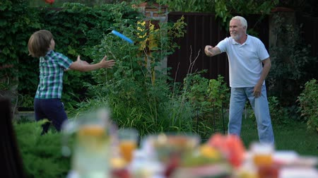 energiek : Kid playing throw and catch game with grandfather, active lifestyle, having fun