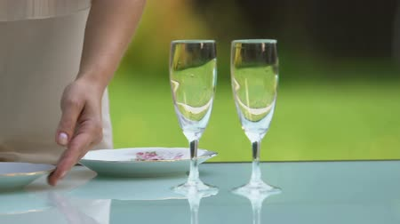 horeca : Female waiter putting plates and glasses on table, outdoor restaurant, catering Stock Footage