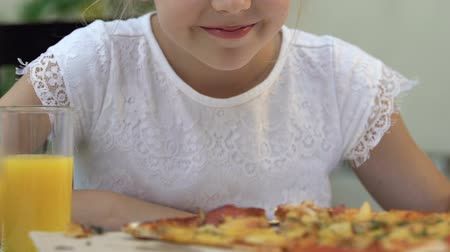откорме : Little girl smelling pizza and smiling, eating junk food, unhealthy nutrition.