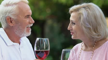 vida : Aged wife and husband enjoying time drinking wine, smiling at camera, marriage