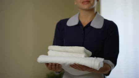 dienstbode : Smiling housemaid turning with clean snow-white towels, hotel rooms booking Stockvideo