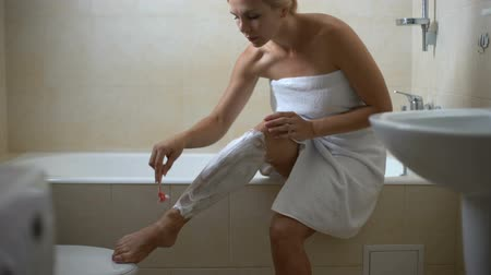 woman waxing : Female covered in towel shaving legs, preparing for date, home spa treatments