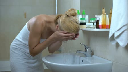 satysfakcja : Lovely lady washes face in front of mirror, satisfied after visiting cosmetician Wideo