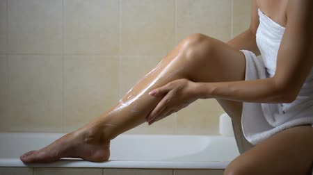 prosedür : Woman massaging and creaming leg with lotion, hydration after depilation at home