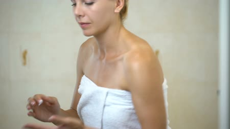 анти : Woman massaging and creaming face with moisturizing lotion in bathroom, home spa. Стоковые видеозаписи