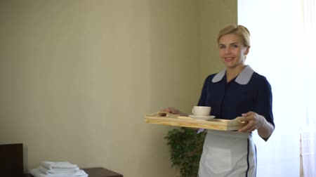 five stars : Chambermaid brings tray with coffee and looks at camera, high quality service Stock Footage