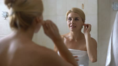 soft tip : Young woman cleaning ears with cotton swab in bathroom, morning procedure health