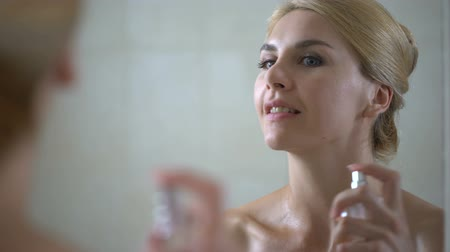 pulverização : Smiling lady in towel sprays perfume on body in bathroom, preparing for date Stock Footage